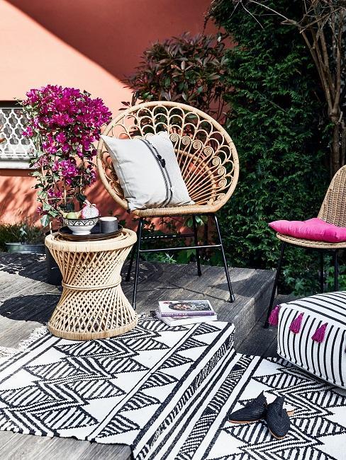 Outdoor Bereich mit schwarz-weißem Boho Teppich, dazu eine Rattan Garnitur