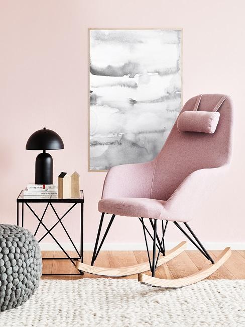 Rosa Schaukelstuhl vor einem hellen Teppich und einer Wand in Rosa mit Wandbild in Grau-Weiß