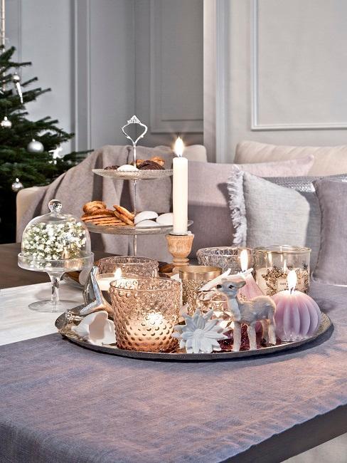 Beisteltisch mit Tischläufer und einem Deko Tablett mit vielen Kerzen und weihnachtlicher Deko, im Hintergrund ein gemütliches Sofa mit vielen Kissen