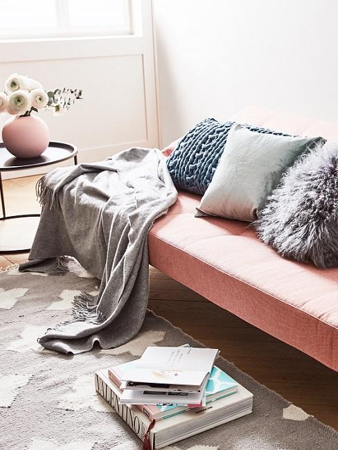Schlafsofa in Rosa mit vielen Kissen und einer Decke in einem hellen Wohnzimmer