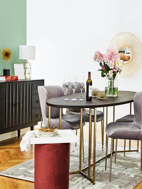 Luxus Esszimmer mit Pouf als Beistelltisch, einem hochwertigen Massivholztisch und einem opulenten Gold-Spiegel an der Wand