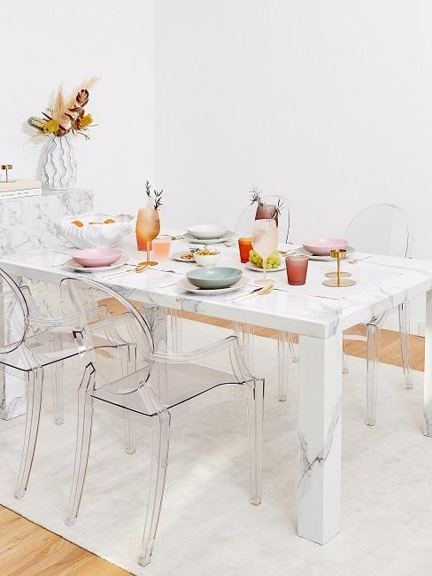Heller gedeckter Tisch mit durchsichtigen Stühlen