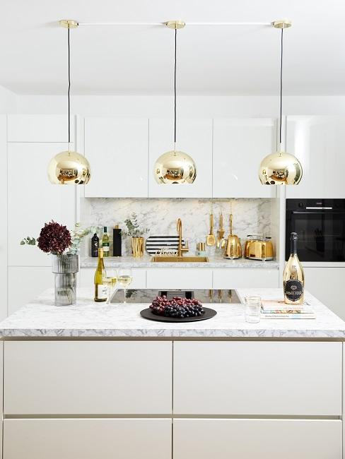 Weiße Küche im modernen Stil mit Marmor Arbeitsplatten und einer Luxus Beleuchtung mit goldfarbenen Lampen