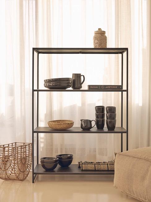 Schwarzes Metallregal mit Geschirr und einem Korb dekoriert