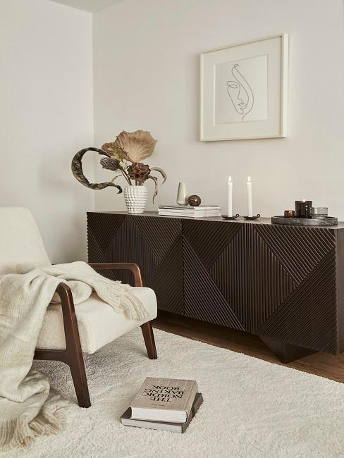 Kolonialstil dunkles Sideboard mit Deko, weißer Teppich und weißer Sessel mit Decke