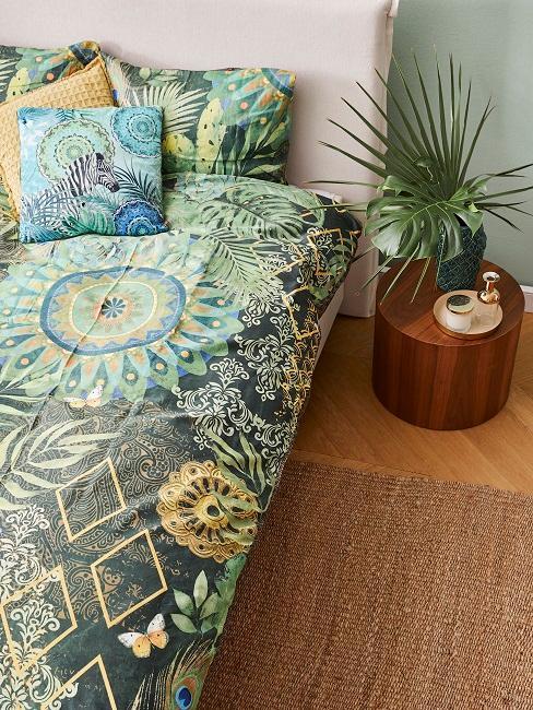 Kolonialstil Bett mit grüner und gemusterter Bettwäsche neben Beistelltisch aus Massivholz und Pflanze