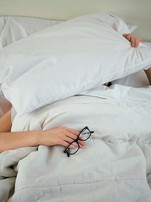 Person mit Brille in der Hand im Bett zugedeckt