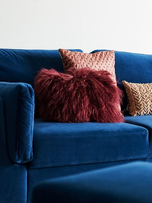 Rote Kissen auf blauem Sofa