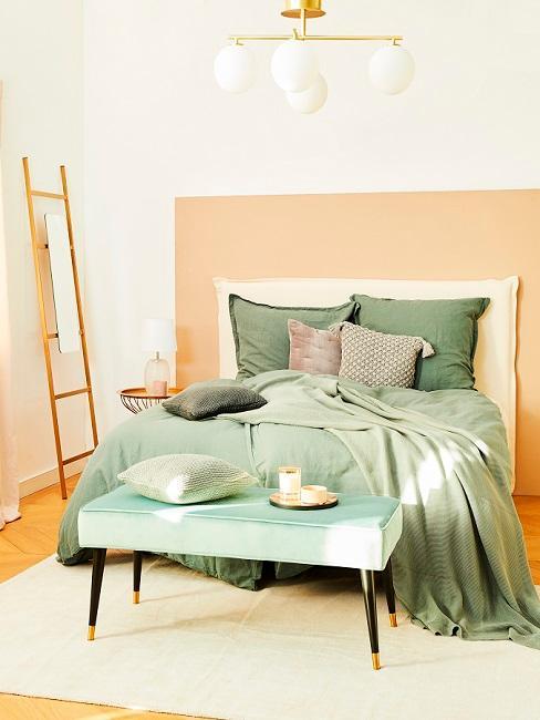 Apricotfarbenes Schlafzimmer mit grüner Bettwäsche
