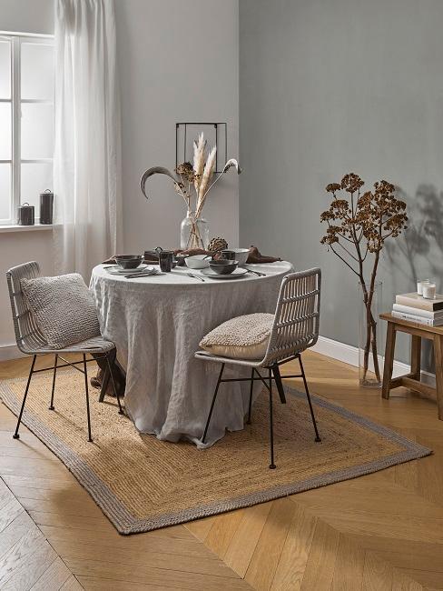 Esszimmer mit hellgrauer Wand und STphlen und Teppich aus Naturmaterialien