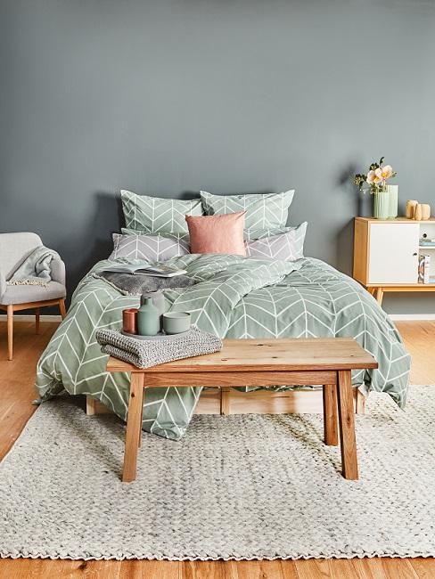 Grau-grüne Schlafzimmerwand mit Holzbank und hellgrüner Bettwäsche