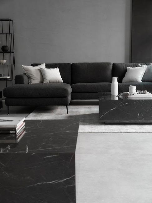 Wohnzimmer in Grau mit schwarzen Möbeln und weißen Kissen