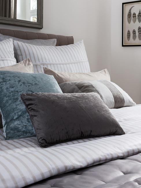 Fünf Kissen auf gestreifter Bettwäsche