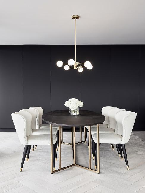 Esszimmer mit schwarzer Wand, weißen Stühlen, goldener Pendelleuchte und dunklebraunem Esstisch