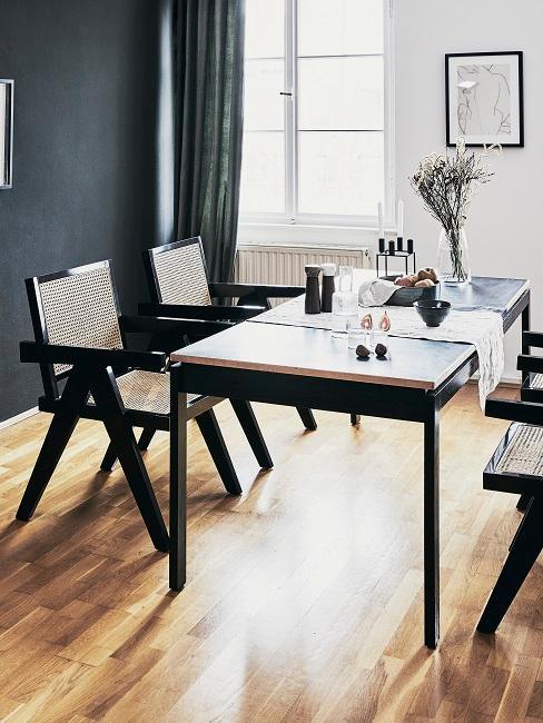 Schwarze Wand hinter Marmortisch und Stühlen aus Wiener Geflecht