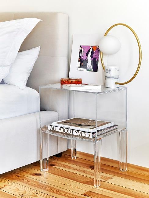 Transparenter Nachttisch neben Bett mit Deko und Büchern