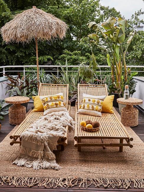 Schöner Balkon im Tropical Style mit Sonnenliegen, Kissen, Juteteppich und Kissen