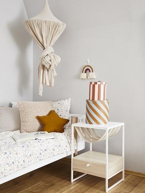 Schönes Kinderzimmer mit Baldachin, bunten Kissen auf dem Bett und Nachttisch