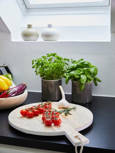 Encimera de la cocina negra con base de madera y tomates en rama