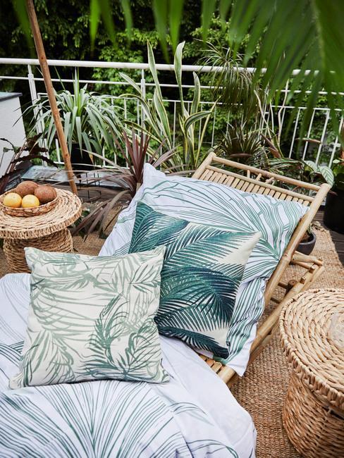 Terraza con hamaca de mimbre y motivos de palmeras estilo tropical