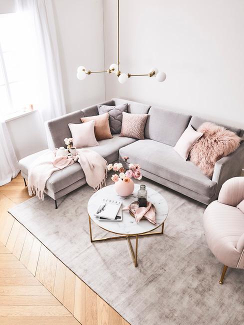 Salón gris y rosa con sofá esquinero grande y cojines