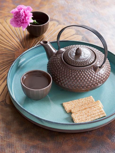 Bandeja azul turquesa sobre mesa de madera con tetera japonesa