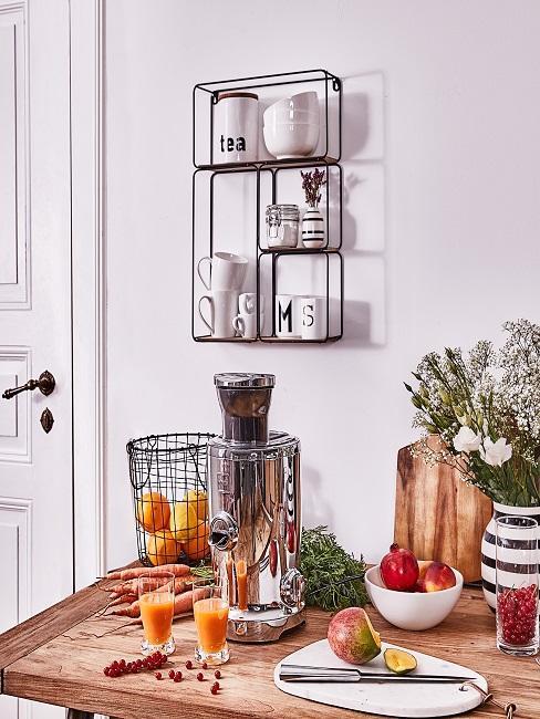Mesa de la cocina con comida, exprimidor de zumos y estantería de pared