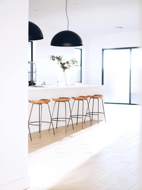 Lámparas de campana grandes en color negro encima de una cocina blanca con taburetes de madera blancos