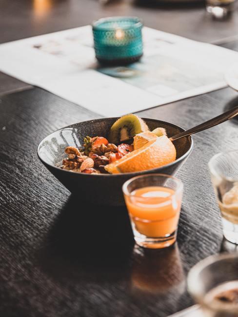 Cuenco y zumo de naranja sobre una superficie de madera de nogal