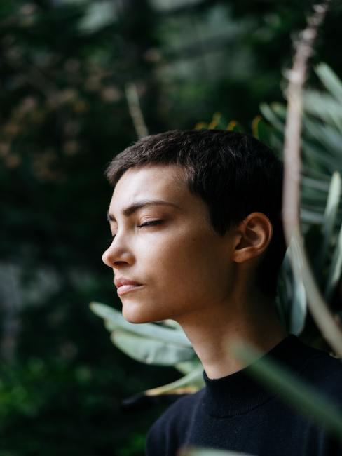 Chica con ojos cerrados en medio de un bosque tropical
