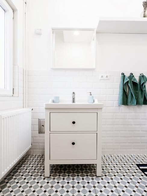 Lavadero blanco luminoso con ventana y cómoda