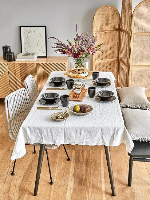 comedor de estilo moderno con piezas de ratán y mesa grande con mantel blanco