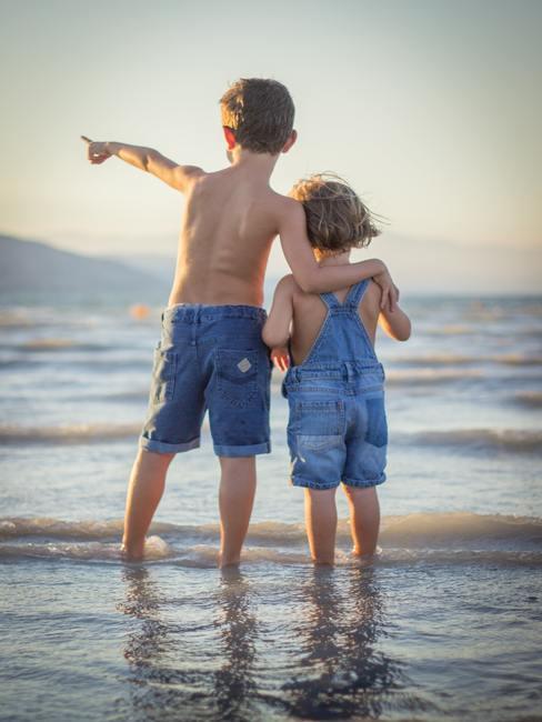 Dos niños en la orilla mirando al horizonte