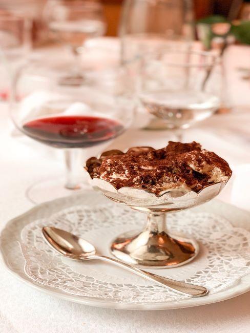 coupe a dessert argentee accompagnie de couillere argentee et un verre de vin rouge, pose sur une serviette de table blanche en dentelle