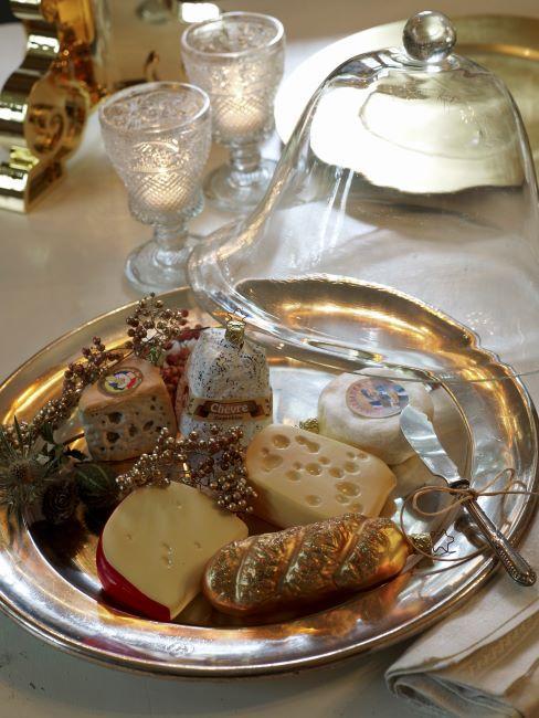 une selection de fromages posee sur un palteau argente accompagne d argenterie et des verres en cristal et une cloche en verre