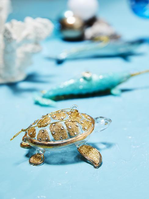 tortue en verre décorative avec écaille texturée dorée sur table bleue