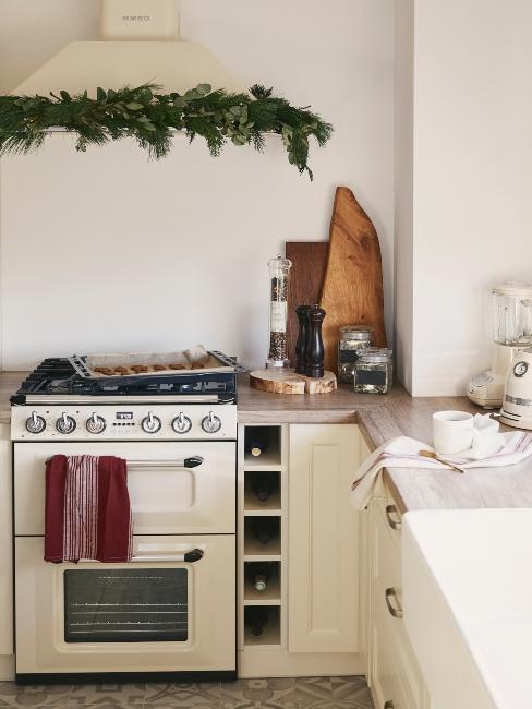 cuinière beige et hotte avec décoration branche de sapin