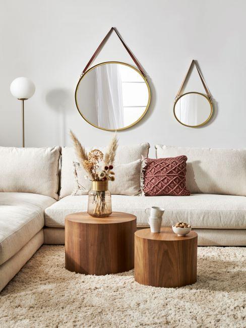 salon boho avec canapes blanc casse et miroirs dores suspendus au mur