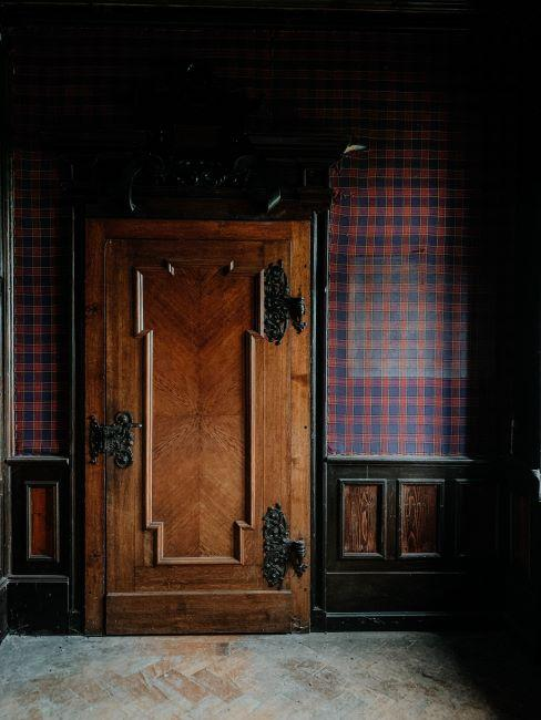 Intérieur ancien avec porte antique en bois et tapisserie tartan
