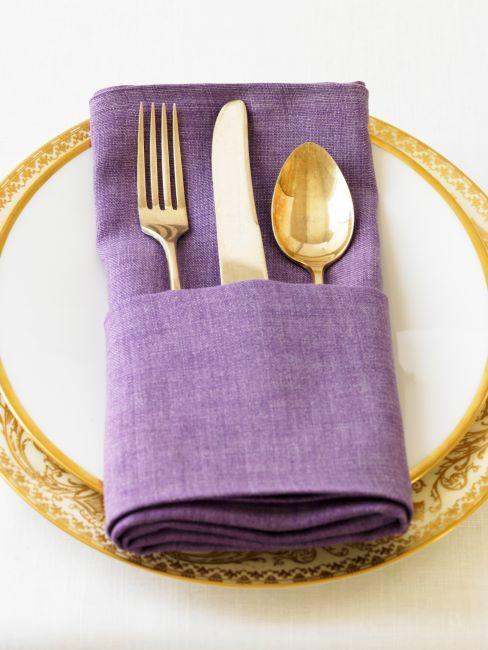 gros plan des assiettes à bord doré et couverts dorés posés dusses emballés dans une serviette de table en tissu violet