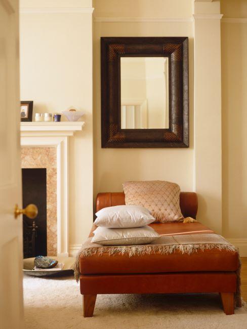 Salon couleur beige avec chaise longue brune et grand miroir en bois