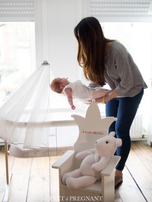 une femme tenant a bout des bras un nourrisson, derriere un berceau avec baldaquin blanc