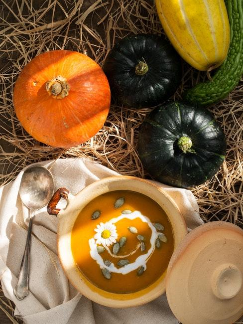 soupe de potiron dans un bol entouree de citrouilles de tailles et couleurs differentes