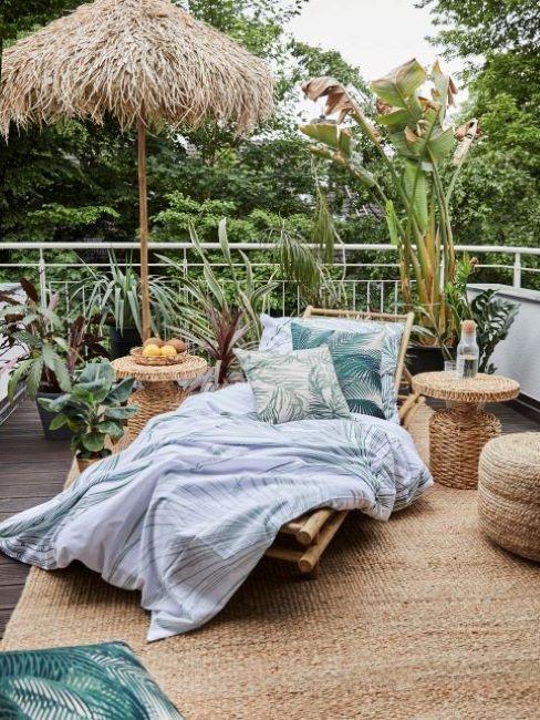 balcone con piante e ombrellone in paglia