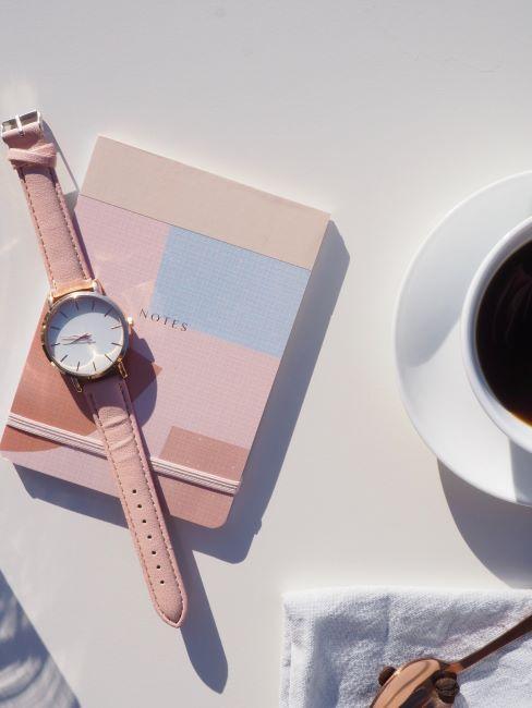 quaderno e orologio rosa vicino a tazza di caffè