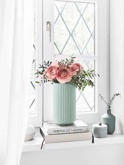 Vaso verde menta con fiori, libri e finestra