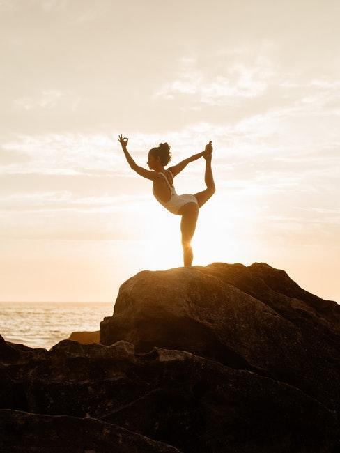 ragazza in costume bianco che pratica yoga al mare