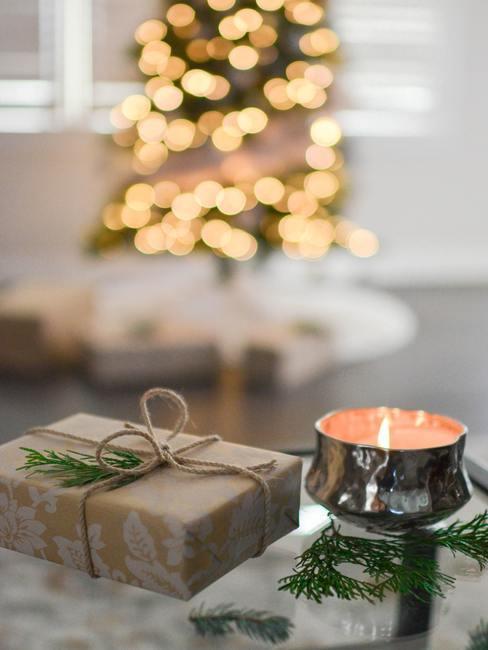 Verpakt cadeau naast een waxinelicht op de achtergrond van de kerstboom.