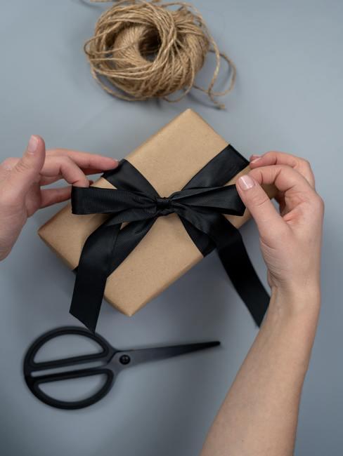 Een ingepakt cadeau met een zwart decoratief lint.