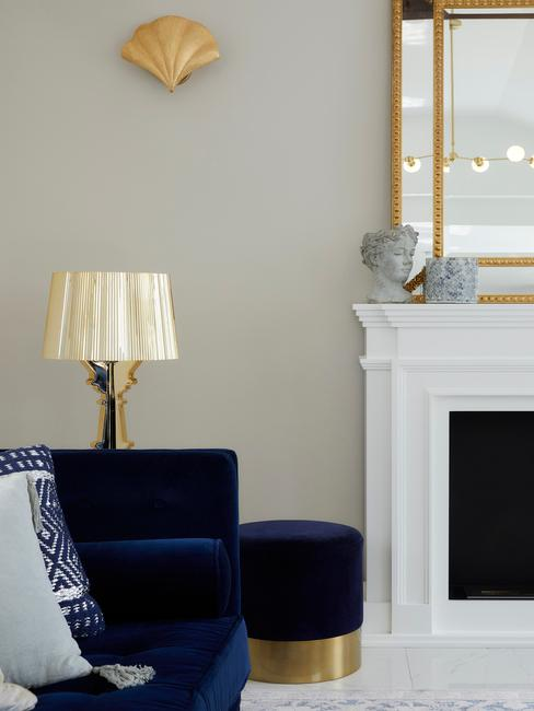 Decoratief object op witte open haard naast een donkerblauwe zitbank en tafellamp